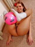 Flexible chick in sheer pantyhose and white socks touches pink ball with her feet