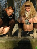 Two fully clothed drunk girls pull down their panties to pee in the woods