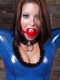Bound beauty with red gag in her mouth poses in blue latex suit in the dungeon
