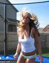 Long haired chick in tight green panties has fun jumping in the backyard