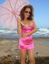 Shapely redhead in tight pink dress and beige pantyhose plays on the beach