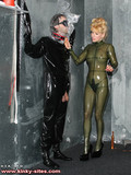 Blonde domina in skin tight rubber outfit loves wrapping up her latex clad slave boy