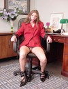 Ballgagged secretary in red suit is tied to office chair and flashes her panties