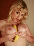 Provoking blonde strips her top and jeans skirt stuffing a big banana between her boobies