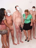 Naked masked guys get their dicks touched by clothed women that want to have sex fun