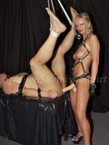 This blonde dominatrix has a heavy strap-on dildo to fuck her slave's ass
