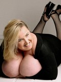 Fat blonde dressed in black shows her her incredibly big boobies on the floor