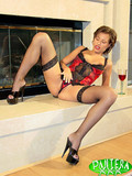 Sexy lingerie model in stockings and high heels poses by the fireplace