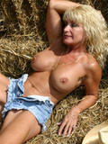 Funny amateur cowgirl gets naked in the haystack and shows melons and pussy