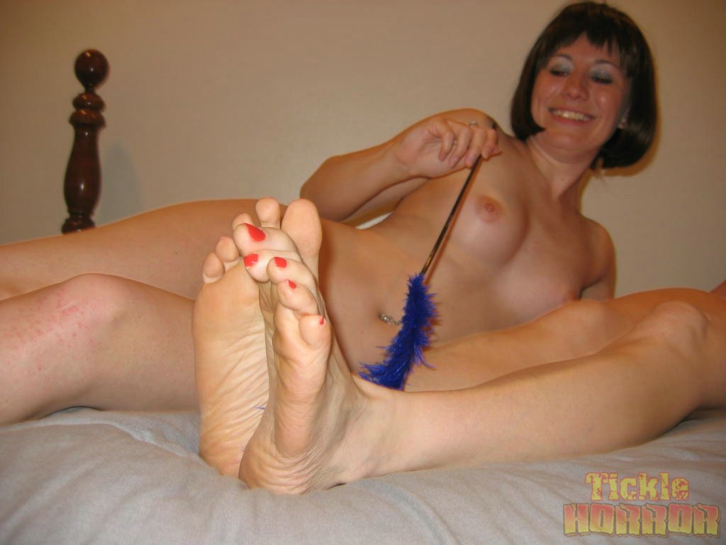 Naked girl gets her feet tickled by nude lesbian domina in ...