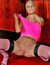 Sexy dressed blonde in pink stretches her pantyhose covering her hand and head in nyloin