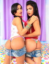 Two sweet dark haired trannies in denim shorts bare their hot asses in front of a dude