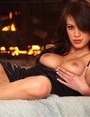 Sexy brunette dressed in black bares her delicious tits by the fireplace