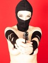 Lady in black mask poses with gun and humiliates naked man on the floor