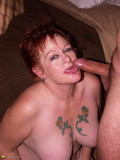 Red-haired granny in black stockings shows her tattooed chest and gets hammered