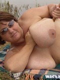 Topless sunglassed woman plays with her gigantic breasts on a blanket by the lake