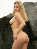 Perfect blonde with stunning big tits and sexiest long legs poses fully nude on the rock