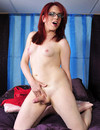 Red-haired four-eyed tranny shows off her tight ass and  lovely dick in these pics