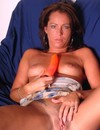 Mature brunette with horny shaved pussy fucks herself with orange rubber dildo